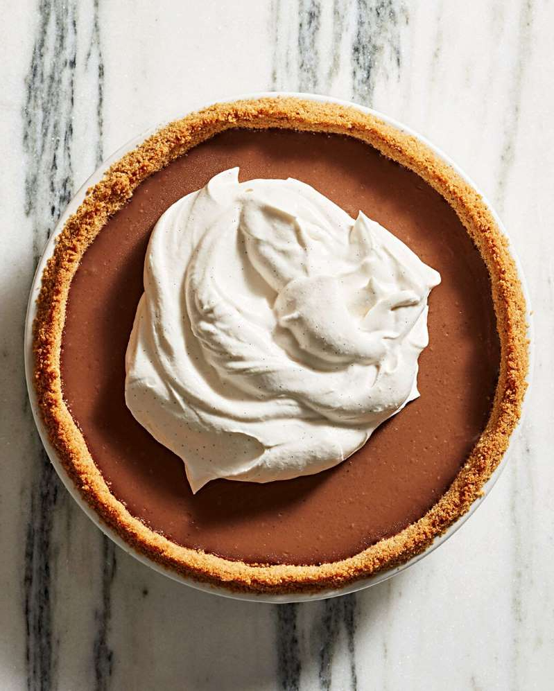 a piece of cake on a plate: milk chocolate pudding pie