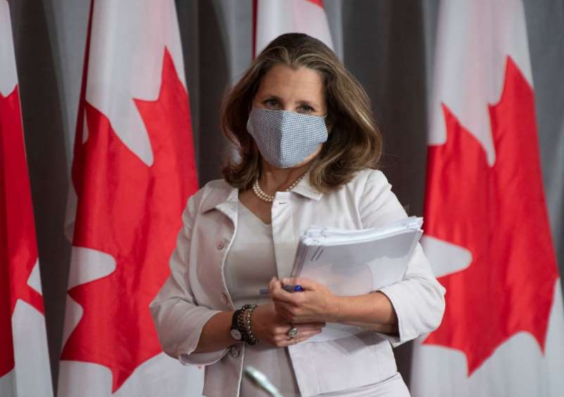 a woman standing in front of a curtain: Deputy Prime Minister and Minister of Finance Chrystia Freeland arrives for a news conference Thursday August 20, 2020 in Ottawa. THE CANADIAN PRESS/Adrian Wyld