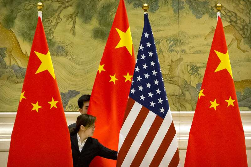 a close up of a flag: Chinese staff adjust U.S. and Chinese flags before the opening session of trade negotiations between U.S. and Chinese trade representatives at the Diaoyutai State Guesthouse in Beijing on February 14, 2019. The world's top two economies managed to cool their trade war with a phase-one agreement at the beginning of this year but escalating tensions sparked in part by the COVID-19 pandemic brought Washington-Beijing ties to an all-time low in the modern era.