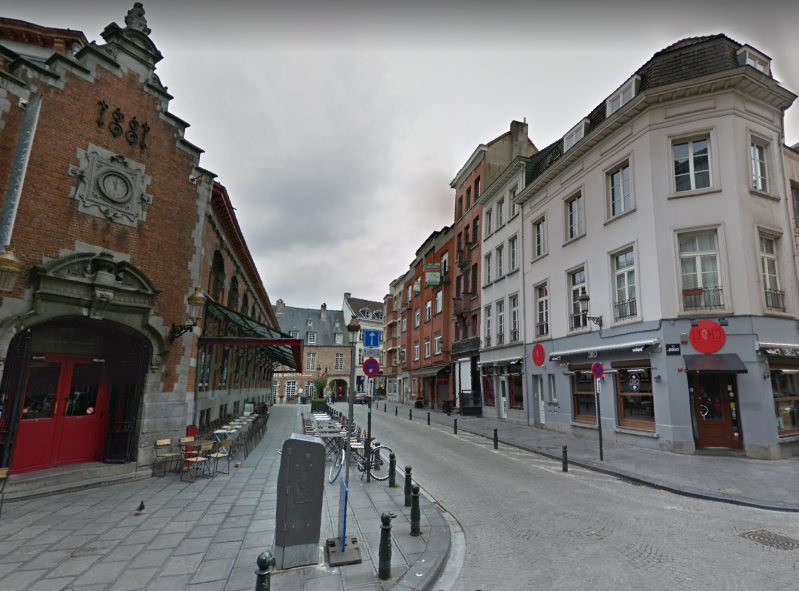 a narrow city street with a clock on the side of a building: The party was broken up by police at an address on rue des Pierres, in the city's gay district.