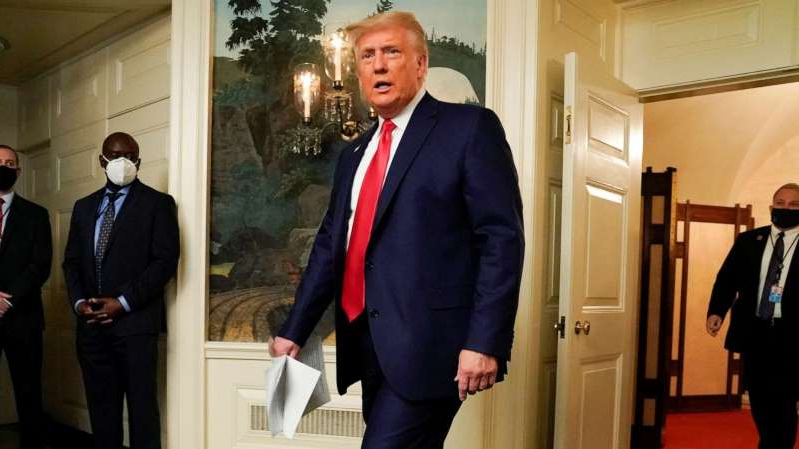 Donald Trump wearing a suit and tie standing next to a woman: President Donald Trump arrives to participate in a Thanksgiving video teleconference with members of the military forces at the White House in Washington, Nov. 26, 2020.