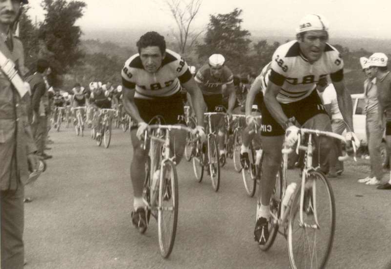 a group of people riding on the back of a bicycle: Aldo Moser (left) riding for the GBC team