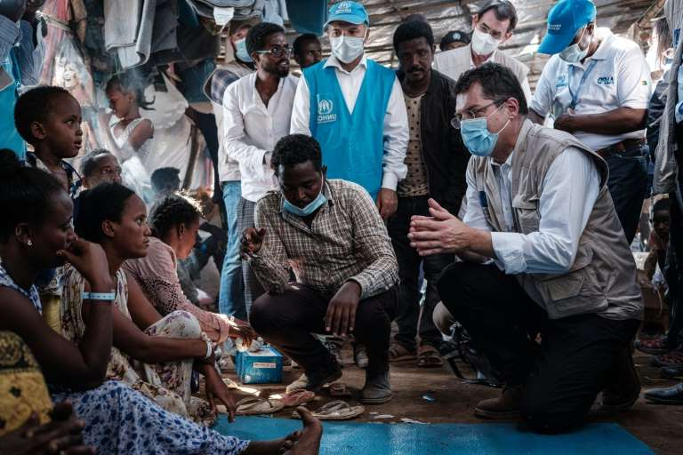 a group of people sitting in front of a crowd: The European Union's crisis management commissioner Janez Lenarcic (L) met with Ethiopian refugees during a visit to the Um Raquba reception camp in eastern Sudan