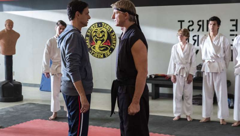 a group of people standing in a room: A still from Cobra Kai season 3
