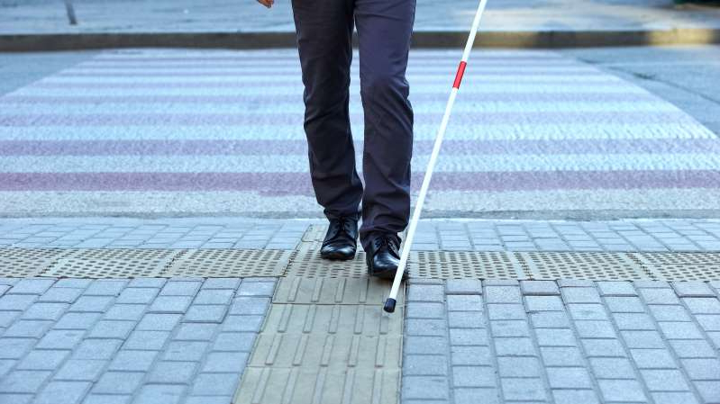 a person walking down a sidewalk: Visually impaired man using tactile tiles to navigate city, finishing crossroad