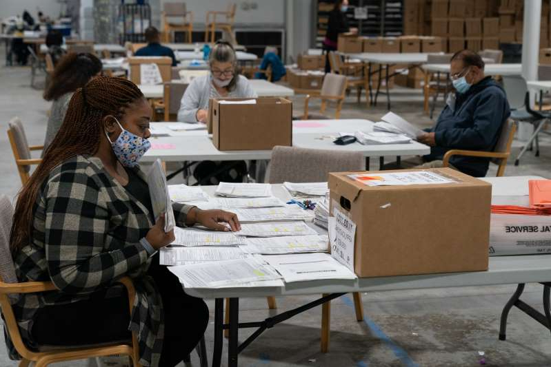 a group of people sitting at a table: Ballots are checked on November 7, 2020 in Lawrenceville, Georgia. A director of Dominion voter systems says he has received death threats following attacks on his company by President Donald Trump.