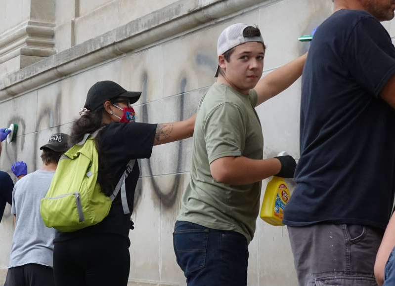 a man and a woman standing in front of a building: Kyle Rittenhouse cleans graffiti from a high school near the Kenosha County Courthouse following another night of unrest on August 25, 2020 in Kenosha, Wisconsin. An attorney for the 17-year-old said he is stepping back from his criminal defense.