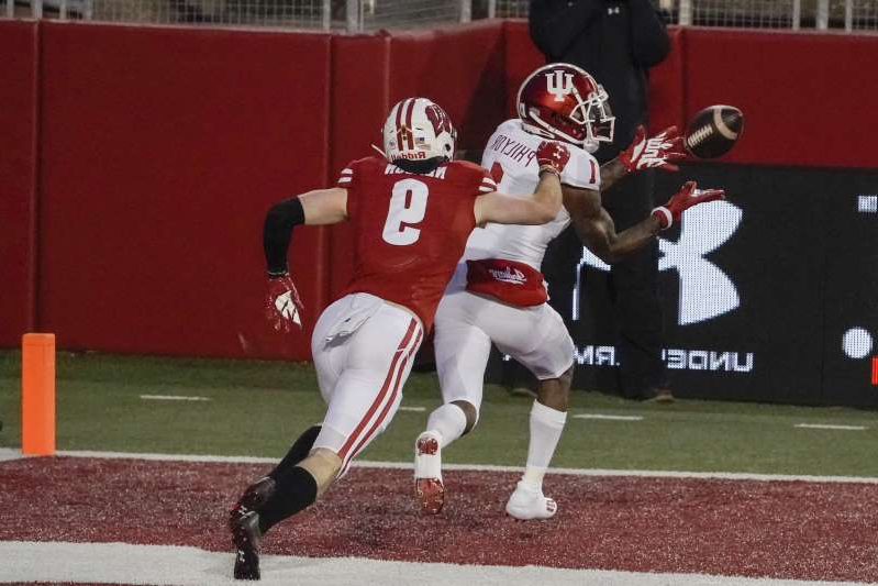 a baseball player taking a swing at a pitch during a game: Indiana's Whop Philyor catches a touchdown pass in front of Wisconsin's Scott Nelson during the second half of an NCAA college football game Saturday, Dec. 5, 2020, in Madison, Wis. (AP Photo/Morry Gash)