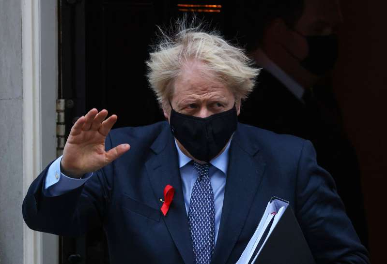 a man wearing a suit and tie talking on a cell phone: Boris Johnson, U.K. prime minister, waves as he departs from number 10 Downing Street on his way to Parliament in London, U.K., on Tuesday, Dec. 1, 2020. Boris Johnson is battling to convince his own Conservative Party colleagues to back plans to keep most of England under strict pandemic controls when the national lockdown ends this week.