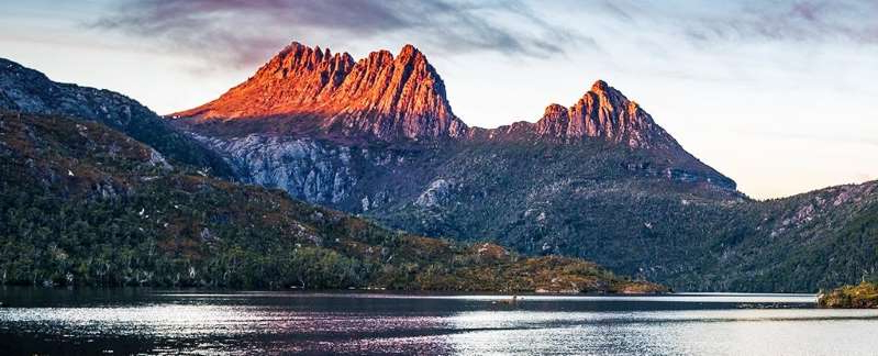 a body of water with a mountain in the background: Cradle Mountain, Tasmania.