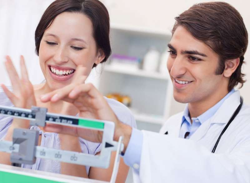 a man and a woman looking at the camera: Woman weight loss doctor scale