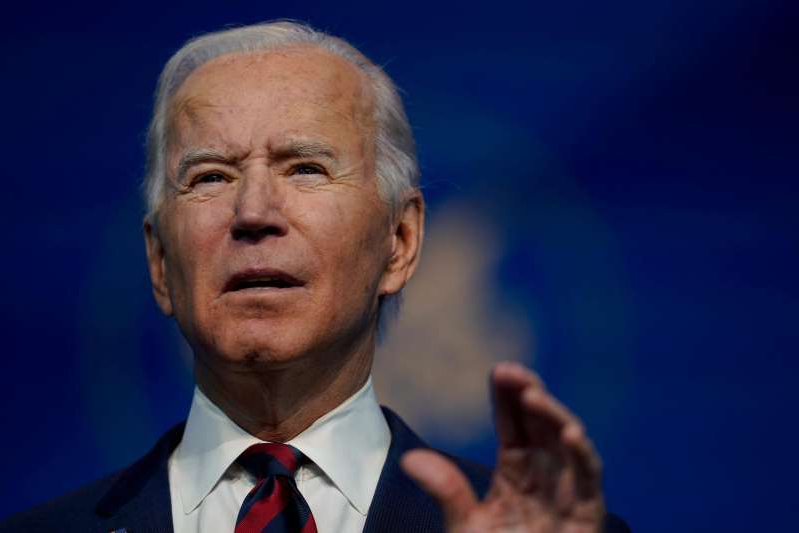 Joe Biden wearing a suit and tie: President-elect Joe Biden speaks at The Queen Theater in Wilmington Delaware, Saturday, Dec. 19, 2020, to announce climate and energy nominees and appointees.