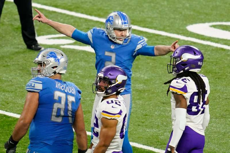 a group of baseball players standing on top of a grass covered field: Detroit Lions kicker Matt Prater (5) reacts after kicking at 54-yard field goal against the Minnesota Vikings in Week 17.