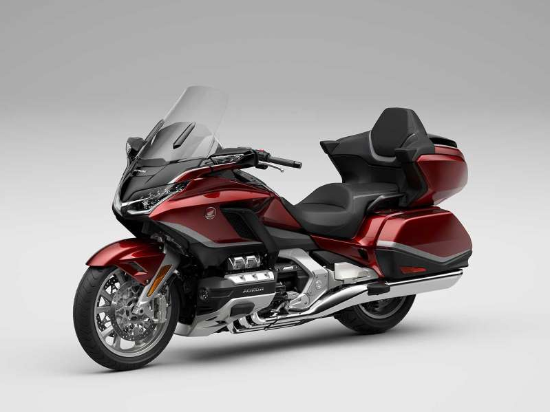 a motorcycle parked on the side of a road: The top-of-the-line 2021 Honda Gold Wing Tour Airbag DCT in Candy Ardent Red. The tour line will have more storage capacity, improved passenger comfort, and an upgraded audio system.