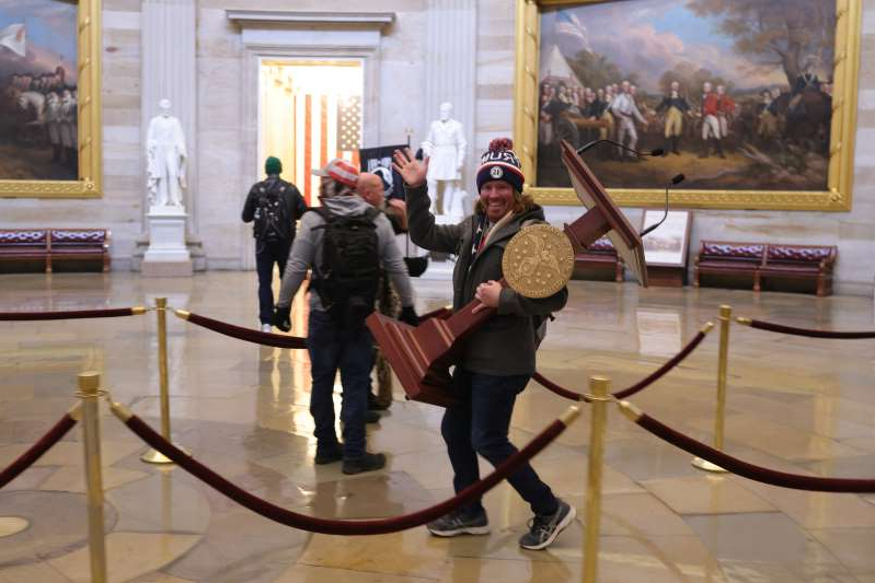 a man and a woman standing in a room: Florida man Adam Johnson carrying Speaker Nancy Pelosi's lectern during the riot at the Capitol. He was arrested on Friday night.