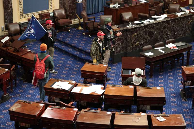 a group of people in a living room: Rioters forced their way onto the Senate floor.