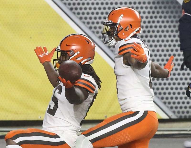 a person holding a baseball bat: Cleveland Browns running back Kareem Hunt (27) celebrates after scoring a touchdown against the Pittsburgh Steelers.