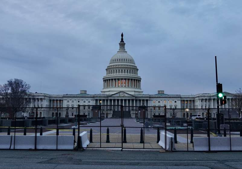 a person standing in front of a fence: New black metal fence surrounds most of the U.S. Capitol building in Washington, D.C., two days after pro-Trump supporters stormed the Capitol. Friday, Jan. 8, 2021