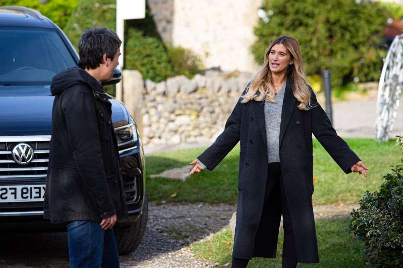 Charley Webb wearing a suit and tie talking on a cell phone: Debbie Dingle and Cain Dingle in Emmerdale