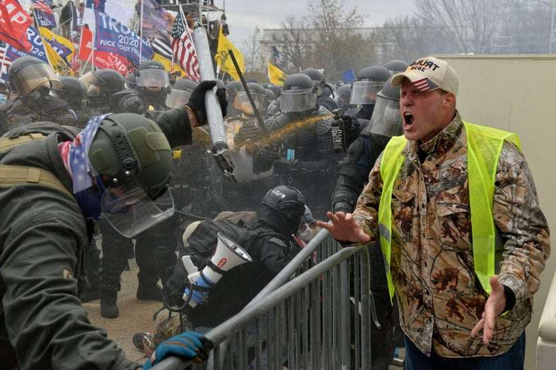 a man in a military uniform: A Trump supporter screams towards police and security forces as rioters storm the US Capitol in Washington D.C on January 6, 2021. Joseph Prezioso/Getty Images