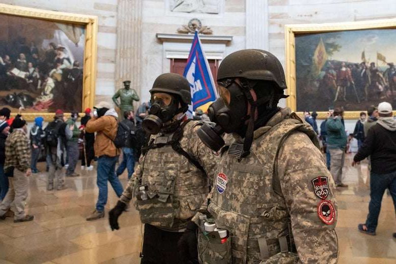 a man in a military uniform standing in front of a crowd: Supporters of U.S. President Donald Trump wear gas masks and military-style apparel as they walk around inside the Rotunda after breaching the US Capitol in Washington, DC, January 6, 2021. SAUL LOEB/Getty Images