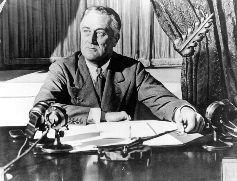 "Franklin D. Roosevelt sitting at a table: President Franklin D. Roosevelt delivers his first radio ""fireside chat"" in Washington in 1933."
