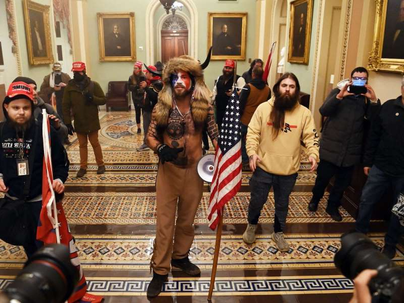 a group of people posing for the camera: Supporters of President Trump in the US Capitol on January 6, 2021. Saul Loeb/AFP via Getty Images