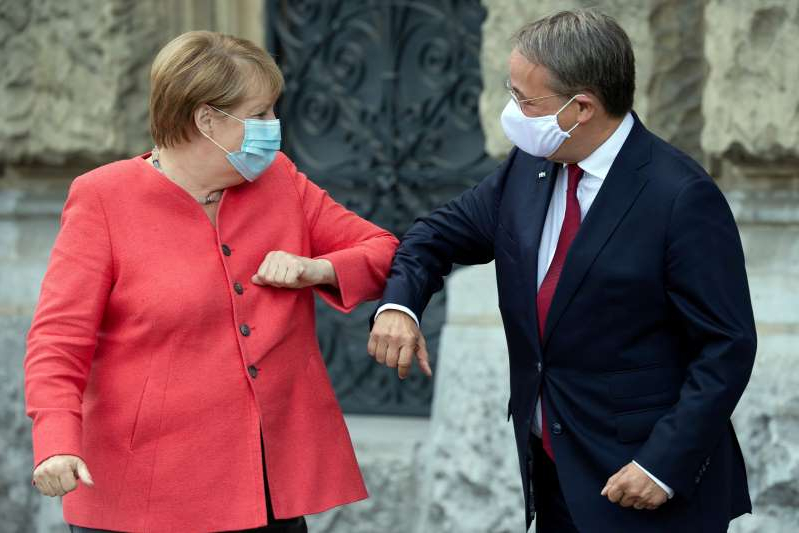 a man wearing a suit and tie talking on a cell phone: German Chancellor Angela Merkel and Armin Laschet, leader of the North Rhine Westphalia state, elbow bump in Duesseldorf, Germany, on Aug. 18, 2020.