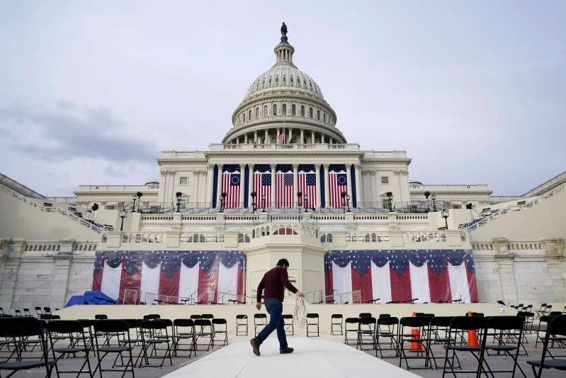 a group of people standing in front of a building: A worker pulls cables as preparations take place for President-elect Joe Biden's inauguration ceremony at the U.S. Capitol in Washington, Jan. 16, 2021.