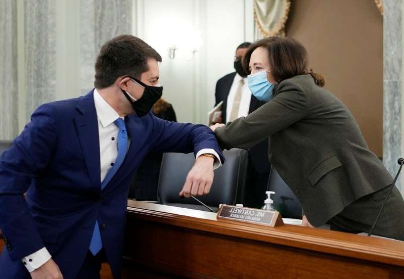 a man wearing a suit and tie: Sen. Maria Cantwell, D-Wash., greets Pete Buttigieg at the Senate Commerce, Science, and Transportation nomination hearings Thursday to consider Buttigieg's nomination to be Secretary of Transportation.