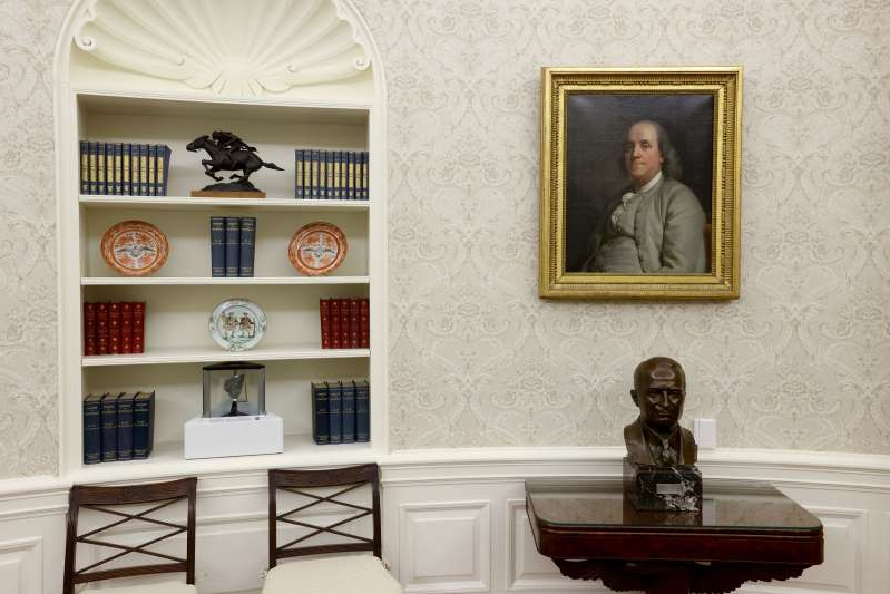 A bust of President Harry S. Truman, a portrait of Benjamin Franklin and a lunar sample share space in the Oval Office of newly inaugurated President Biden on Jan. 21. (Reuters/Jonathan Ernst)