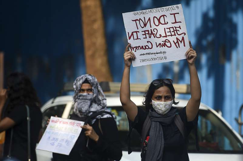a person holding a sign: Activists hold placards during a protest to condemn the alleged gang-rape and murder of a 19-year-old woman in Bool Garhi village of Uttar Pradesh state, in Mumbai on October 6, 2020. Authorities in Uttar Pradesh's capital city Lucknow are planning on installing facial recognition cameras in an attempt to stem harassment of women.