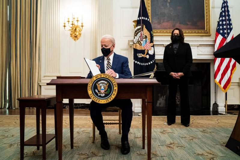 a person standing in front of a statue: President Biden, with Vice President Harris by his side, signs executive orders at the White House on Jan. 22.