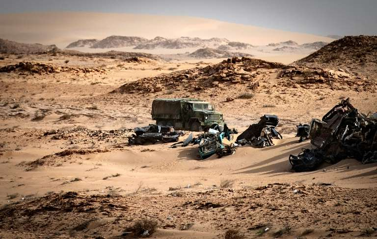 a man riding a motorcycle down a dirt road: Morocco launched a military operation on November 13 in the buffer zone of Guerguerat, in the extreme south of Western Sahara, to drive out a group of Saharawi militants who were blocking a transit route to neighbouring Mauritania