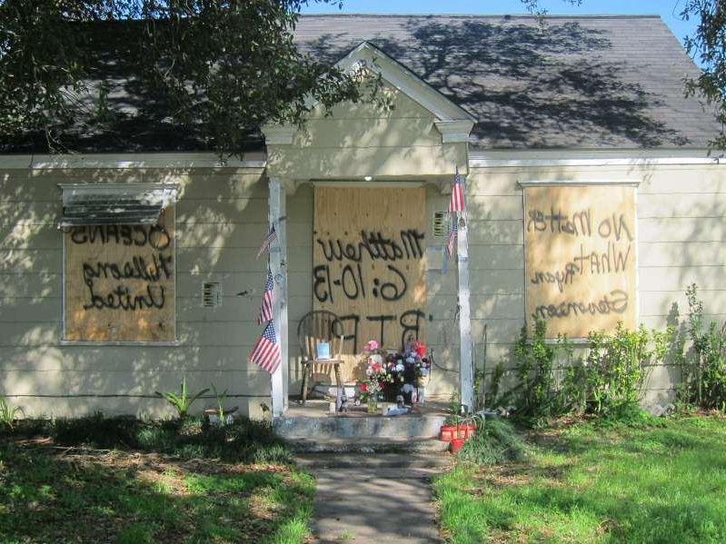 a house that has a sign on the side of a building: A makeshift memorial is set up in February 2019 at a Houston home where two people were killed during a drug raid that year. (Juan Lozano/AP)