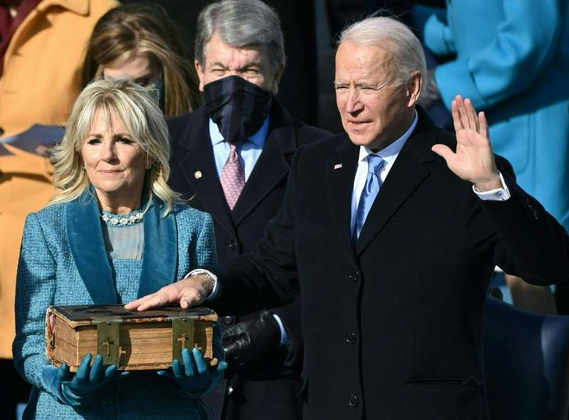 Jill Biden wearing a suit and tie talking on a cell phone: President Biden takes the oath of office as his wife, Jill Biden, holds his Bible on Jan. 20. (Brendan Smialowski/AFP/Getty Images)
