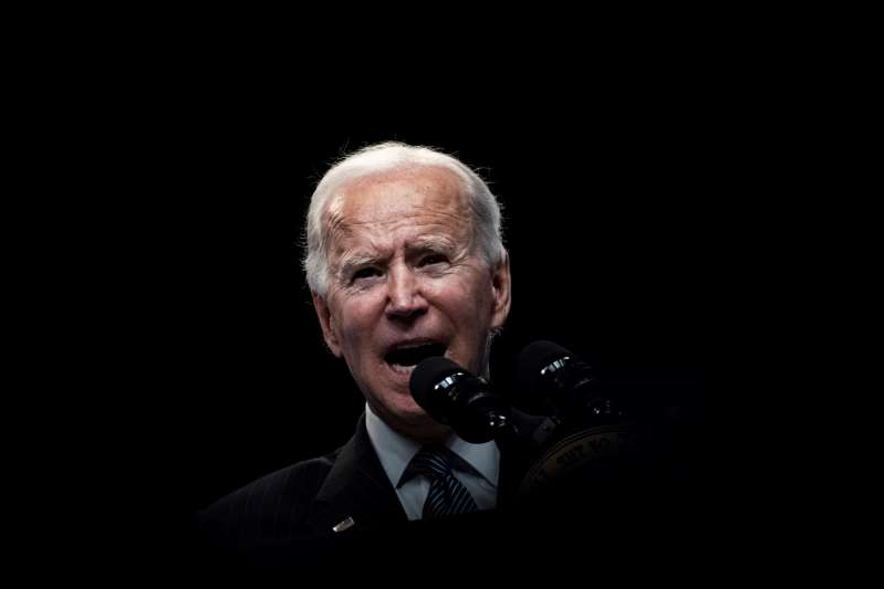 Joe Biden wearing a suit and tie: President Biden speaks about American manufacturing before signing an executive order in the South Court Auditorium of the White House complex on Monday.