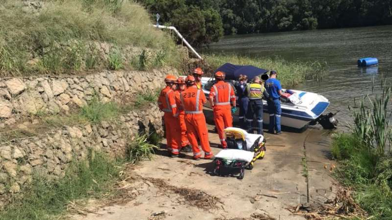 a group of people on a dirt road: The couple lost control of the boat when a spider dropped down from the roof. (Supplied: NSW Ambulance Service)