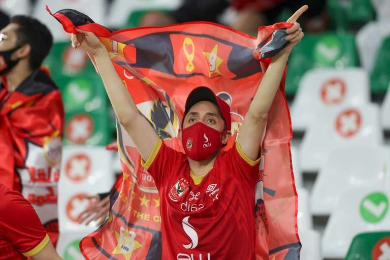 a group of people wearing costumes: An Al-Ahly fan cheers on their side at their first FIFA Club World Cup clash against Qatar's Al-Duhail