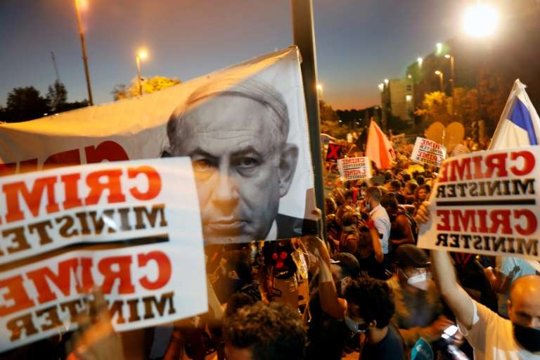 Benjamin Netanyahu et al. standing in front of a sign: Weekly protests against Netanyahu have rumbled on for months, with demonstrators from the 'Crime Minister' movement focusing on graft allegations the premier faces