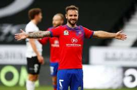 a man holding a football ball: Blackburn Rovers' Adam Armstrong celebrates scoring their fourth goal v Derby County