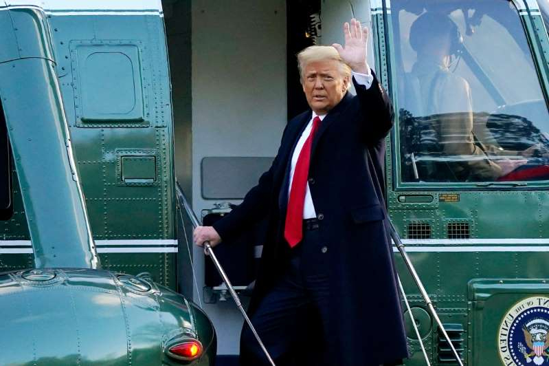 Donald Trump standing in front of a car: Former President Donald Trump waves as he boards Marine One on the South Lawn of the White House on Jan. 20, 2021.