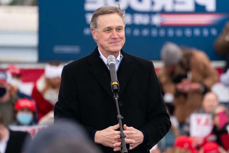 David Perdue wearing a suit and tie: Former Senator David Perdue has filed paperwork with the Federal Election Commission to leave the door open for a possible 2022 run against Georgia Senator Raphael Warnock. In the photo above, Perdue speaks at a Defend The Majority campaign event attended by U.S. Vice President Mike Pence on December 17, 2020 in Columbus, Georgia.