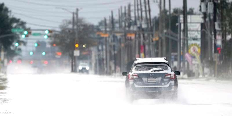 a car driving down a street next to a snow covered road: Vehicles drive on snow and sleet covered roads on Monday in Spring, Texas.
