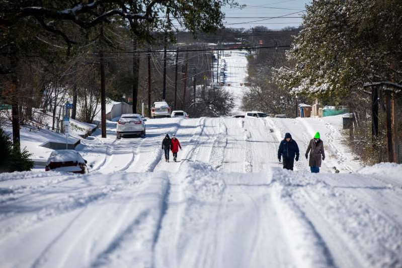 a group of people cross country skiing in the snow: Pedestrians walk on an icy road on February 15, 2021 in East Austin, Texas. Winter storm Uri has brought historic cold weather to Texas, causing traffic delays and power outages, and storms have swept across 26 states with a mix of freezing temperatures and precipitation.