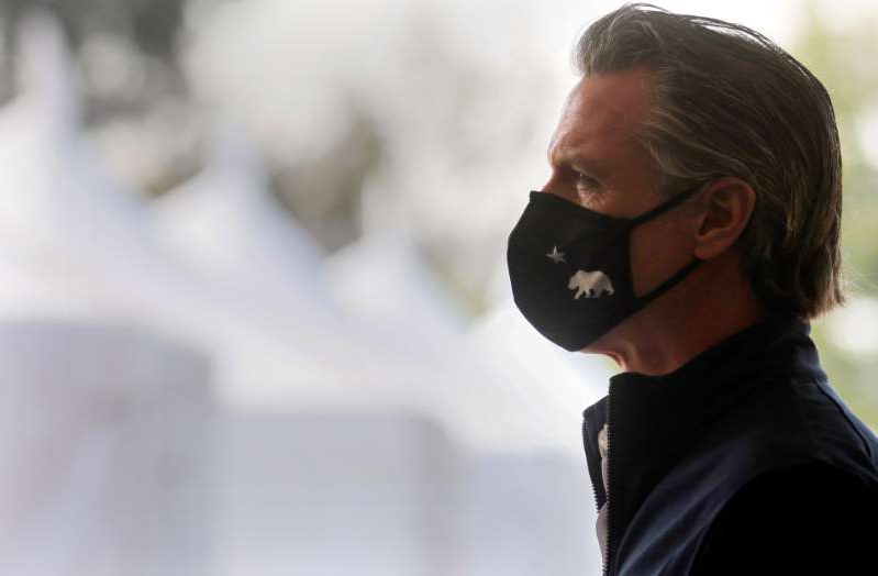 a close up of a person wearing a mask: Democratic strategists who are familiar with the last recall election in California do not believe the recall campaign California Governor Gavin Newsom is facing will be successful in ousting him. In the photo above, Newsom enters a press conference following the opening of a new large scale COVID-19 vaccination site at Cal State Los Angeles on February 16, 2021 in Los Angeles, California.