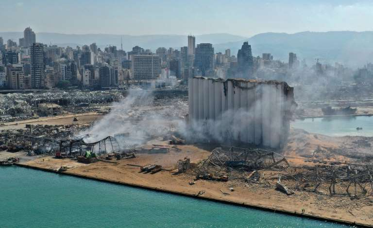 a body of water with a city in the background: Beirut's port was left devastated by a massive blast on August 4