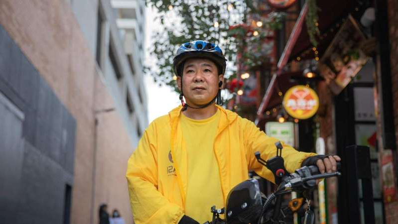 a man wearing a hat: Former rider Xiangqian Li said he was sacked by the delivery giant without a warning. (ABC News: Jack Fisher)