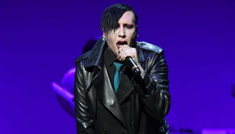 Marilyn Manson wearing a suit and tie talking on a stage