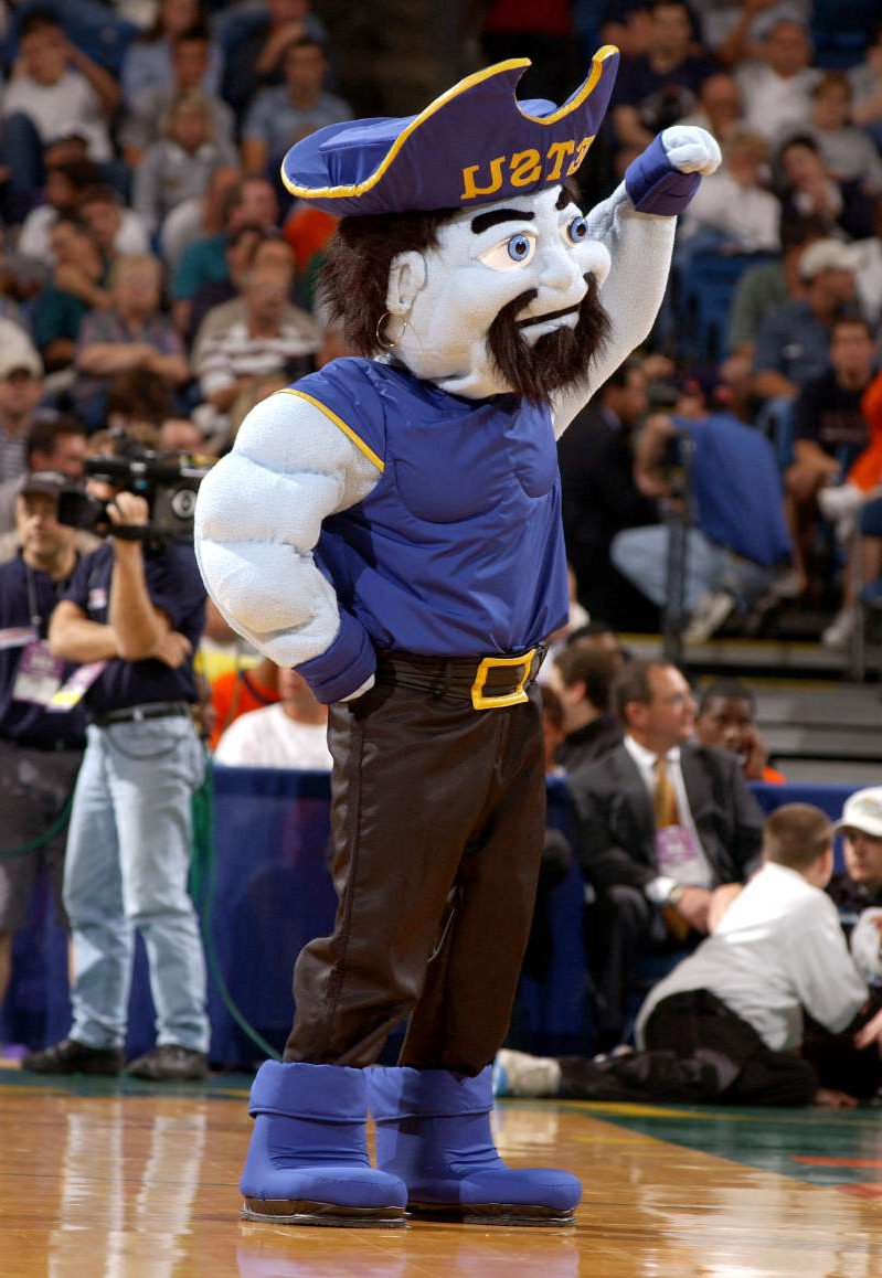 a person standing in front of a crowd: Tennessee lawmakers expressed disappointment after the players on the ETSU men's basketball team kneeled during the national anthem to support racial justice. Here, the mascot for the E. Tennessee State Bucs cheers for his team on March 21, 2003 in Tampa, Florida.